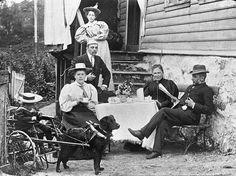 Et familiebilde i Gravdal, Bergen 1895. Bilde er tidstypisk for familieportrettet, gjerne tatt utendørs ved en trapp eller i hagen. Bildene er ofte komponert for å vise sosial status, og relasjoner. Dette bilde stikker seg ut i mengden med den interessante vognen. Kan det være en tidlig «motorisert» rullestol, eller et leketøy for barnas fornøyelse. Den er en viktig del av bilde og må ha hatt en betydning for familien. En nyvinning eller egenprodusert? Fotograf Ukjent. Billedsamlingen - UiB 12th Century, The St, Capital City, Bergen, Thing 1 Thing 2, West Coast, Norway, Medieval, Survival