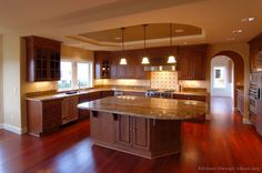 This contemporary kitchen features a reddish glow. The floor is red with cherry wood finishing. The brown wooden cabinet and island is covered on top with extended marble countertop. The low hanging lights and low spotlights below the cabinets lit up the room.