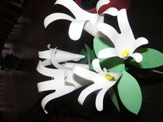 Draw a child's handprint on white paper and cut out. Curl and tape thumb to small finger. Slide a green pipe cleaner into the bottom of the flower. Add green leaves. A beautiful bouquet of lillies.