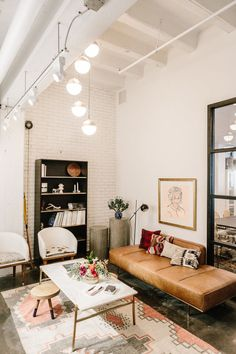 Boho studio living room. Exposed brick walls, tan leather couch, and blush pink patterned rug