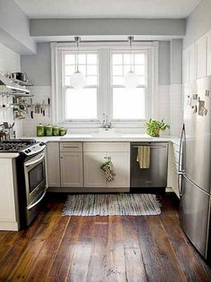 Landelijke keuken met moderne apparatuur en een antieke houten vloer.