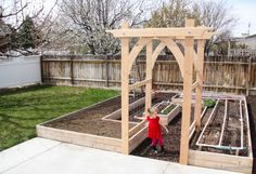 L-shaped garden beds with beautiful semi-Gothic arbor. Even better if there are two, one at each 'entrance' to the veg. patch. Possibly enclose the whole patch with trellis walls, so you can grow more verticals, AND keep out the blasted pooping cats!