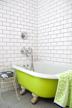 floor to ceiling white subway tile are used as a background to this vintage chartreuse painted claw-foot tub.