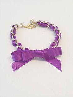 Pulsera en cadena de color dorado brillo, con cinta de raso violeta, adornado con un lazo.