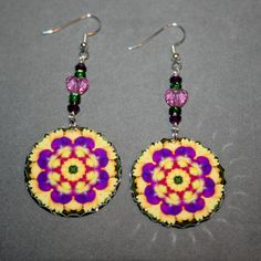 Dangle earrings adorned with my purple pansy on a yellow daisy boho chic mandala new age sacred geometry hippie kaleidoscope design titled Blissful Beliefs <br /> <br />These lightweight, dainty silver earrings begin with a dangle of two amethyst biscone Swarovski crystal beads, two kelly green Czech glass beads and a rose heart Swarovski crystal bead that accentua...