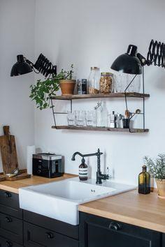 W kuchni postawiono na czarne szafki stojące z drewnianymi blatami. Z kolei wolna ściana bez szafek wiszących daje...