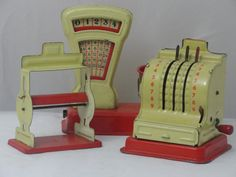 Vintage tin grocery store toys, with cash register, paper dispenser, and scale.