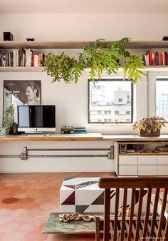 Home Office integrado com a sala tem prateleiras de concreto e marcenaria na cor branca.