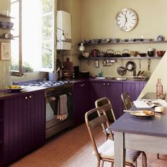 Marie Claire Maison. In this Parisian loft, it's the lower cabinets that got bathed in purple, giving the eat-in country-style kitchen a shot of urban chic.