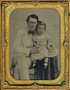 It doesn't get any better than this! Look at the way the child grabs onto her father's thumbs.  RUBY GLASS AMBROTYPE. Ambrotypes are positive images on glass, and need a black backing in order to be seen. The exception is ruby glass ambrotypes, on colored glass, which need no black backing. This is a ruby glass ambrotype.  DATE. The ambrotype era is generally considered to be 1854-1863.  SIZE. Half plate size (approximately 5 1/2 x 4 1/4 inches).  HOUSING. Black thermoplastic case…