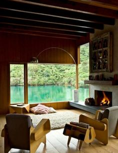 http://www.justsoakit.com/wp-content/uploads/2015/02/cozy-design-ideas-wood-burning-fireplace-with-wide-glass-window-view-ocean-as-well-white-fur-rug-on-floor-plus-wooden-chair-870x1129.jpg