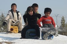 Afghan children use water containers as sledges as they slide down a snow-covered hilltop overlooking Kabul on January 9, 2014. As winter sets in across Central Asia, many Afghans struggle to provide adequate food and shelter for their families. AFP PHOTO/SHAH Marai