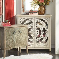 A piece of beautiful lace must have been the designer's inspiration for our Kieren Cabinet. With its romantic flourishes and bows in each corner, it's destined to be the focal point in any room, and no two are exactly alike. Handcrafted of whitewashed wood, the carved design is backed by clear glass doors that open to a handy storage shelf.