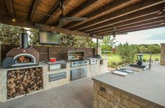 Little Horn Residence In Frisco, Texas  I love this gourmet kitchen! It includes wood burning pizza oven, grill, side burner, egg smoker, sink, refrigerator, trash chute, serving station and more!  via Houzz from AquaTerra Outdoors
