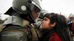 A imagem foi tirada no dia 11 deste mês no Chile, durante protestos que marcaram o 43º aniversário do golpe militar, e representa muito mais do que uma simples disputa visual entre uma manifestante e um policial.