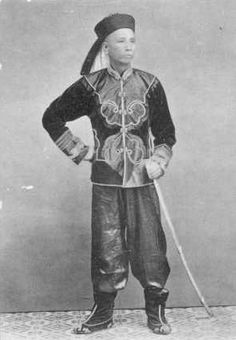 Chinese Qing Dynasty officer, circa 1900.  The soldiers dressed in traditional Chinese uniforms, carried an assortment of weapons . Many carried old Austrian muskets, Martinis ,Mausers and Enfields rifles but often with incorrect ammunition. Others were armed with ancient weapons, mainly bows and arrows and long spears The morale of the Chinese armies was generally very low due to lack of pay and prestige, use of opium, and poor leadership .
