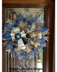 Ivory and jute Burlap are used in pouf method and denim  mesh was  used as a ruffle layer which gives this wreath a country chic. It is loaded with white polka dots and navy  burlap ribbons. Tiny blue denim balls are used for accent.  The tin cross with the denim flower pull it together.