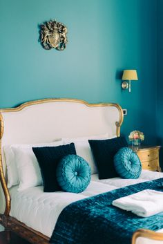 Thicket Priory Lady Isobel's Room, with midnight blue walls and a crest, a double bed with a linen headboard and gold furnishings Blue Room Decor, Blue Rooms, Blue Walls, Room Decor Bedroom, Bedroom Ideas, Linen Headboard, Linen Bedroom, Gold Bedroom, Luxurious Bedrooms