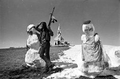 AIM activist with rifle stands guard in front of Sacred Heart Church with two freshly built snowmen after a blizzard at Wounded Knee. The church was later burned down, 1973  Photo credit: Jim Hubbard — in Wounded Knee, South Dakota.