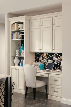 A built-in desk with bookcase and cabinets creates a seamless home office in a…