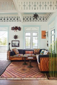 A white living room with vintage furniture in clashing prints in reds and oranges with pale blue and white walls.