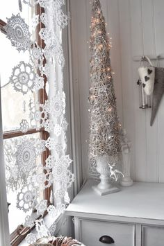 Crocheted snowflakes sewn together in long lines hang in the window. Inspiration in white