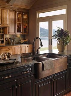 Dark and Handsome Who says you can't mix woods? This cozy, masculine kitchen goes all-in with both maple and walnut cabinetry and a deep, oak-front farmhouse sink. French doors provide just enough light to show off the room's varied textures – from the wood grain to the tile to the granite counter tops.