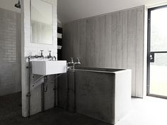 open shower . simple sink . concrete bathtub . industrial & sparse . walls of: wood, tile, and brick . glass door . beautiful light