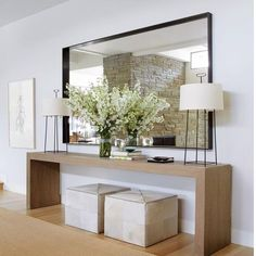 Such a great vignette for a foyer. Recipe for success: long & lean console table + ottomans that can be pulled out for extra seating as needed + greenery + statement lamps + a few thoughtful accessories + oversized mirror. Easy substitutions: baskets instead of ottomans, art instead of mirror. By @timothywhealon . . . . . #interiordesign #interior123 #interiorinspo #housetour #decorcrushing #foyerdecor #maketimefordesign #entrytable #foyergoals