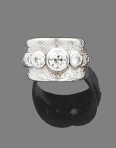A diamond three-stone ring  The wide band with engraved foliate details, collet-set to the front with three graduated old brilliant-cut diamonds, diamonds approx. 1.00ct. total