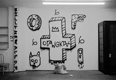 "a black and white photograph that depicts a room with a graffiti ridden wall centered in the composition and lying face up on the floor. the symmetrically balanced photograph is sharp and focuses on the figure which is the graffiti. the art on the wall depicts grunge-like features with 5 main figures. first in the hierarchy of figures is an upside down crucifix with ""OFWGKTA"" written on it in crude graffiti writing. The anti crucifix is made 3D using a parallel drawing system."