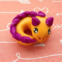 Polymer Clay Charm: Orange and Purple Dragon.  This is from JLeanneCreations at Etsy.  Only five bucks - for all this charm. In a charm. A charming charm. Chaz - don'tcha love it?