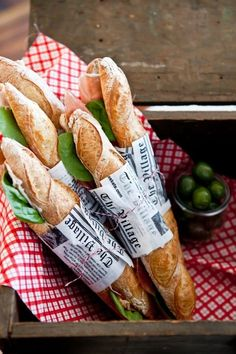 baguette sandwiches filled with cold cuts and leafy greens in french newspaper.