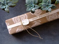 Celery heart stamp on plain brown paper, tied with natural twine, hand stamped ribbon andd a polymer clay stamped gift tag