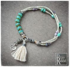 Three strands of sterling washed seed beads, with assorted crystalssprinkled throughout, flow into a focal group of milky turquoise glass. With fine silver accents, clasp, leaf charm and cotton tassel. Leave your exact wrist measurement above, before adding to cart.