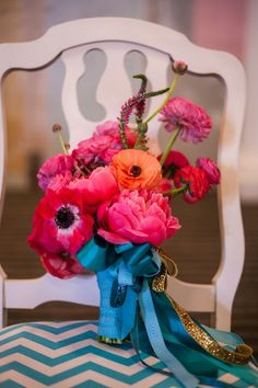 Hot pink and orange flowers with blue ribbon.