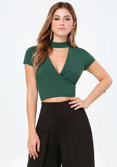 Bold crop top with a sexy deep V front and surplice silhouette. Mock neck creates a choker look. Back neck button-loop closures. Partially lined.