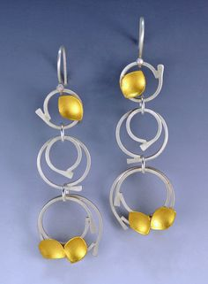 Cosmic Rings Earrings by Judith Neugebauer. These earrings are crafted out of sterling silver circles, adorned with 23k gold leaf pods. Silver is available with an oxidized or satin finish.