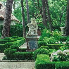 Boxwood hedges, limestone walkways, statue on patinaed cast iron pedestal