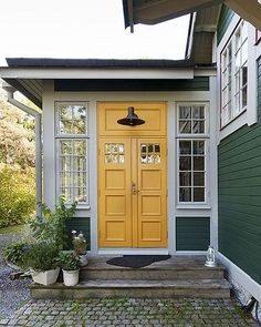 Green, white and a bright yellow double front door! Charming and fresh entry, front door, porch, and a brick path or walkway to the BEST colors! Yellow Front Doors, Double Front Doors, White Doors, Exterior Paint, Exterior Design, Interior And Exterior, Cottage Exterior, Swedish Cottage, Swedish House
