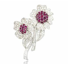 A RUBY AND DIAMOND DOUBLE-CLIP BROOCH   Designed as two entwined flowers, the bombé circular mixed-cut ruby centres to brilliant-cut diamond petal surrounds, raised on curving baguette-cut diamond stems, with similarly set leaf accents, circa 1950, 7.5cm long