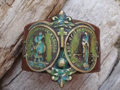 "BLaME IT ON MY GYPSY SoUL......WoNDeRFuL, ReCYCLeD BRoWN LeATHeR WiTH THaT GReAT SLiGHTLY WoRN LooK. A BiG, 3 1/4"" GoRGeOUS, BRaSS ReLiGiOUS MeTaL, RiVeTED ON WiTH HaND APPLiED PaTiNAS. ONE SiDE FeATuRES SaINT CHRiSToPHeR, THE PaTRoN SaINT OF TRaVeL. THE OTHeR SiDE SaY'S, LaDY OF THE HiGHWaY PRoTeCT US.We MaKE ALL OuR CuFFS FRoM ReCYCLeD LeATHeR BeLTS, PiCKeD UP AT THRIFT SToRES, WITH ALL OF THeiR QUiRKS AND FLaWS.*ReCYCLE*RePuRPoSE*"