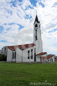 Modern built white church with red roof photographed on a cloudy summer day. Church is located in front of buildings and on a large grass area.