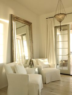 bedrooms - white linen pinch-pleat drapes French doors silver leaf floor mirror white slipcover accent chairs white drum table  Monochromatic