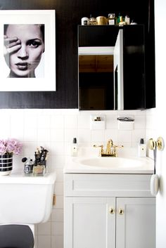 Black and white bathroom with fashion art, lilac roses, and mirrored cabinet