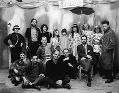 A cast photo for Claes Oldenburg's Circus: Ironworks/Fotodeath, performed at the Reuben Gallery, Feb, 21–26, 1961, with Edgar lakeney, Max Baker, Tom Wesselmann, Claes Oldenburg, Henry Geldzahler, Clifford Smith (seated, left to right); Gloria Graves, Carl Lehmann-Haupt, Olga Adorno, Pat Oldenburg, Marilyn Jaffee, Judy Tersch, Claire Wesselmann, Chippy McClellan, Lucas Samaras (standing, left to right). Photo © Robert R. McElroy/Licensed by VAGA, New York, New York
