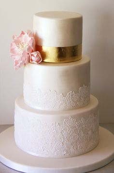Elegant ivory lace wedding cake with gold leaf and pearl shimmer. Vintage style edible lace.