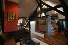 S tmavými tóny přírodního dřeva přirozeně ladí částečná zástěna v červeném tónu. #interiordesign
