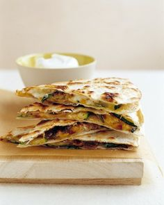 Zucchini Quesadillas    4 tablespoons olive oil 1 onion, coarsely chopped Salt 4 cloves garlic, minced 2 medium zucchini (about 1 pound), halved lengthwise and thinly sliced crosswise 1 cup frozen corn kernels (4 ounces) 1/4 cup chopped fresh cilantro (optional) 4 (8-inch) flour tortillas 2 cups grated pepper jack cheese
