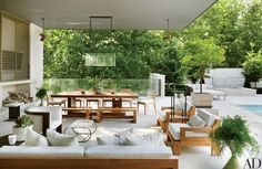 A poolside lounge features a pendant lantern by Ames Ingham and a barrelback chair from Dennis Miller Assoc. | archdigest.com